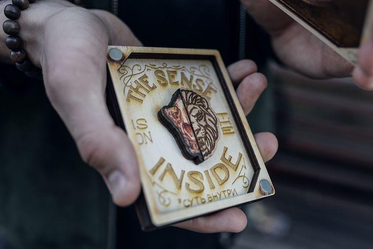 """Значок """"Лев"""" в подарочном деревянном кейсе из новой коллекции Under the skin. Надпись «Sense is on the inside» («Суть внутри») размещена внутри. Размер кейса 10,5 х 8,5 см. Крышка крепится на магнитах."""