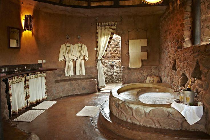 African Lodge Bathroom, screed/concrete floor, concrete bath tub, stone wall finish