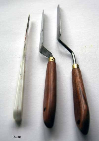 Many people confuse painting knives and palette knives. On the left is a palette knife (for mixing paint on the palette), centre is a metal and wood palette knife and on the right is a painting knife - it has a larger bend in the handle to allow the paint to be applied to a surface without your fingers touching already applied, wet paint.