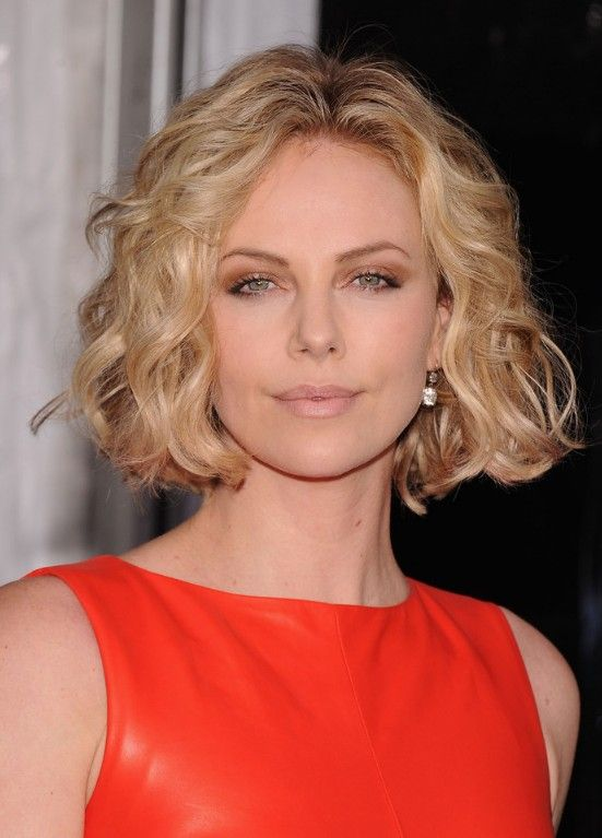 Blonde with dark roots and jaw length wavy curly bob haircut and a center part hairstyle.