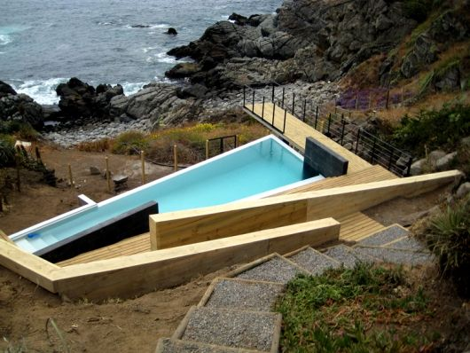 Pool Terrace in Quintay, Chile by Tomas Garcia de la Huerta - contrast of light timber with dark tile and angular wrapping forms