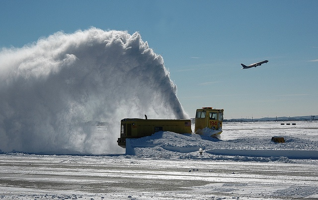 A snow blower does its work at Boston Logan International Airport