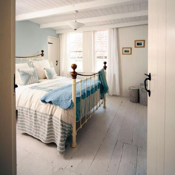 Fresh bright double bedroom with painted wooden floorboards and sumptuous bedding make this bedroom in Wortley Cottage very inviting!