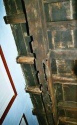 Draagbalk van de zoldervloer achter de voorgevel in een 18e-eeuwse boerderij. De uitsparingen, de niet doorlopende kleine zolderbalkjes en de zwarte vlekken op de balk wijzen op de oorspronkelijke plaats van de voorgevel onder deze draagbalk.