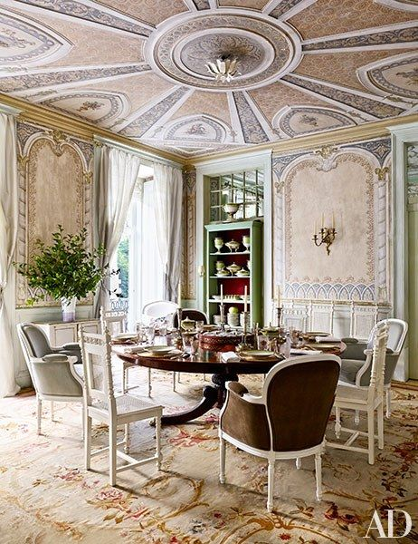 In the dining room of this Lisbon house, Victorian side chairs and vintage bergères surround a mahogany pedestal table atop an Aubusson carpet; a leafy light fixture centers the ceiling, though Espírito Santo prefers to dine by candlelight. | archdigest.com