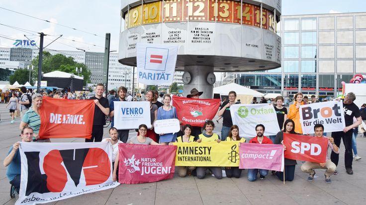 Menschen halten Transparente mit den Logos verschiedener NGOs  vor der Weltzeituhr auf dem Alexanderplatz in Berlin. Zu sehen sind folgende Organisationen: Die Linke, VENRO, Paritätischer Wohlfahrtsverband, NaturFreunde, Oxfam, Brot für die Welt, Lesben- und Schwulenverband, Naturfreundejugend, Amnesty International, campact und SPD.