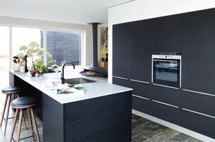Mustaksi petsattua tammea. Ohut vaaleanharmaa komposiittipöytätaso lähes leijuu huoneessa. Tässä Seurustelukeittiössä® allas on keskellä työskentelysaareketta, joka muodostaa keittiön luonnollisen keskipisteen.