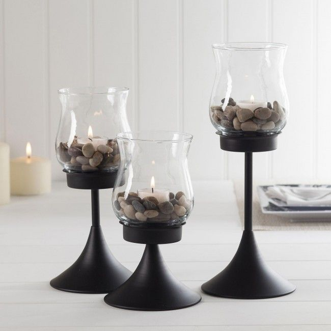 Add ambience to any room with our Spire Tealight Hurricane candleholders. Featuring a sturdy metal base and classic tulip shaped glass bowl that protects the candle's flame, this set of three hurricane style tealight holders will provide mood lighting for any occasion. Place all three candleholders together for a bright focal point or spread them throughout your room for a more subtle lighting option.