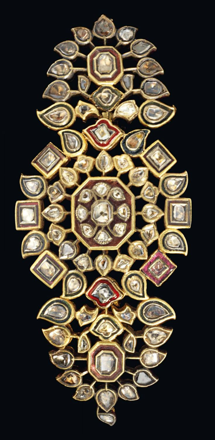 AN ENAMELLED AND DIAMOND-SET GOLD BAZUBAND NORTH INDIA, 19TH CENTURY Of typical form with a central rosette composed of diamond-set rectangular, drop-shape and palmette segments radiating around a central octagonal plaque, with hinged semi-circular elements on either side, similarly inset, the reverse decorated in polychrome enamel with a floral design, attachment loop on one end, repairs to the hinges 2 x 4½in. (5 x 11.5cm.)