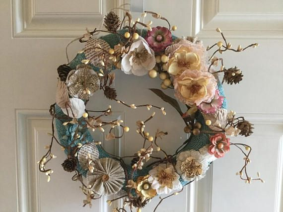 "Spring wreath, 12"" WREATH - 12 all season wreath on styrofoam wreath form, wrapped with blue burlap ribbon and embellished with multi color flowers and leaves. A pretty garland is wound around the wreath. The garland is bendable and may need to be rearranged after being received due to"