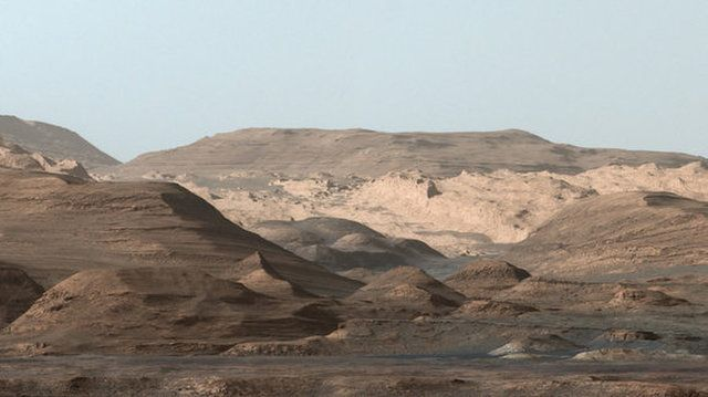 """From NASA: """"This composite image looking toward the higher regions of Mount Sharp was taken on September 9, 2015, by NASA's Curiosity rover. In the foreground ― about 2 miles (3 kilometers) from the rover ― is a long ridge teeming with hematite, an iron oxide. Just beyond is an undulating plain rich in clay minerals. And just beyond that are a multitude of rounded buttes, all high in sulfate minerals. The changing mineralogy in these layers of Mount Sharp suggests a changing environment in…"""