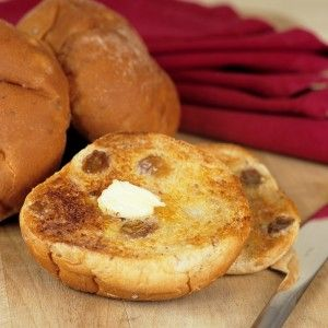 Teacakes on a chopping board with one slit open and buttered with a knife.