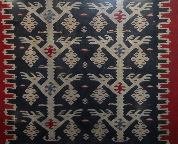 "Пиротски ћилим ""Гугутће на диреци"". Pirot kilim is a unique, authentic and highly regarded brand of flat tapestry-woven carpets or rugs, made of pure sheep's wool from Stara Planina, southeastern Serbia, dyed with natural colours and long enduring. It is made as a single piece, has 28 weave lines in 1cm and both sides of the rug can be used. Its colors, patterns and ornaments are unique: 96 of them are geographically protected. Pirot kilim is made exclusively in Pirot, Serbia."