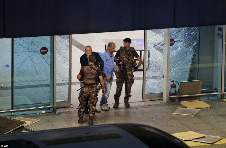 Turkish police officers stand outside Istanbul's Ataturk airport, where scores of people h...