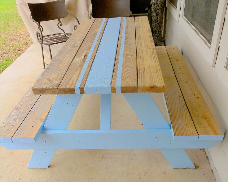 Picnic table with runner.  We planned to paint it all blue, but when we stood it up after painting the underside, we really liked the natural weathered wood look with the blue, so we just painted a runner on top instead. That was the easy part! (Please see the next photo for instructions). We sanded the sides and top of the table smooth and paint-free to display the natural wood. On the seats, we left the paint on the sides.