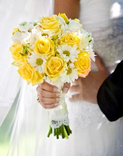 Bright yellow roses add a burst of color to an otherwise all-white bouquet of ranunculus, mums, freesia and peonies.