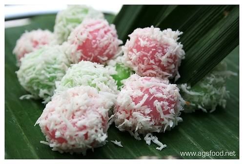 Klepon~ Boiled rice cake, stuffed with coconut sugar, and rolled in fresh grated coconut. It is flavored with pandan leaves juice.