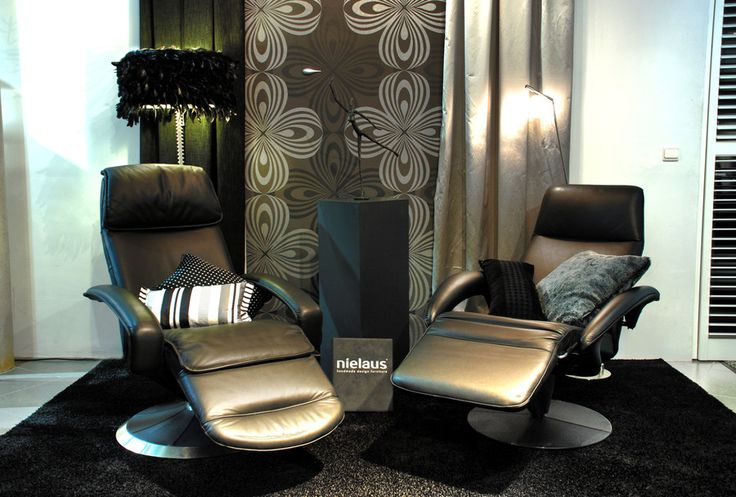 2 Recliners in a show room, designed by Steen Ostergaard produced by Nielaus in Denmark. Made of leather I don't really know why people add throw pillows to these lounge chairs? as they are only in the way, as these recliners are ergonomically correct shaped, so you don't need any pillows.