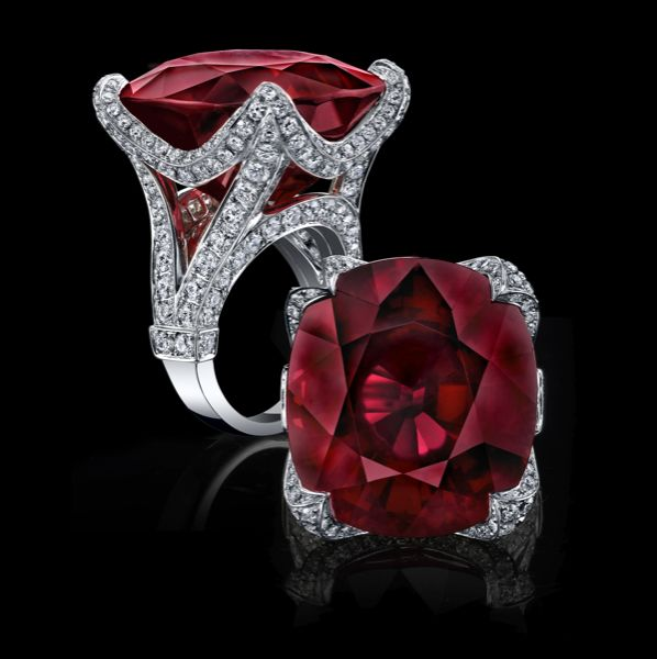 A deep red rubellite gem of a magnificent 42.82cts is expertly set in a hand sculpted 18K white gold regal mounting reminiscent of the Eiffel tower from the side and accented with 4.12ctw of white diamonds.