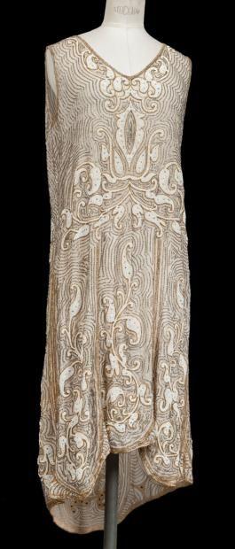ANONYME, circa 1925  Robe en lin beige entièrement rebrodé de perles tubulaires argent, or, de perles blanches et de strass à motif d'inspiration indienne, decolleté en pointe, sans manches, jupe à longueur asymetrique (petits manques) - CORNETTE DE SAINT CYR