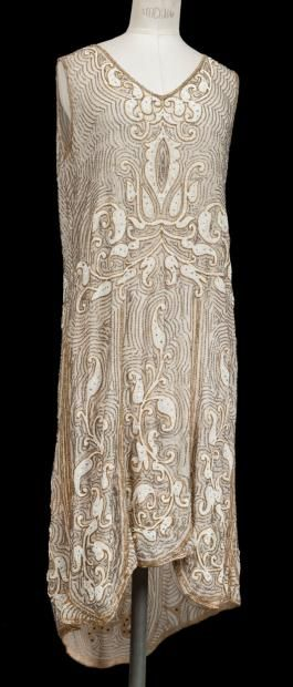 Beige linen dress, ca. 1925, entirely covered with gold & silver bugle beads, faux pearls, & rhinestones in an Indian-inspired design. Asymmetric length skirt.