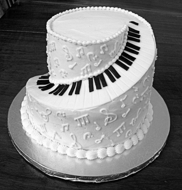 "This is a 10"" & an 8"" butter cream cake carved to look like a spiral piano is winding up the side. Piano keys are fondant."