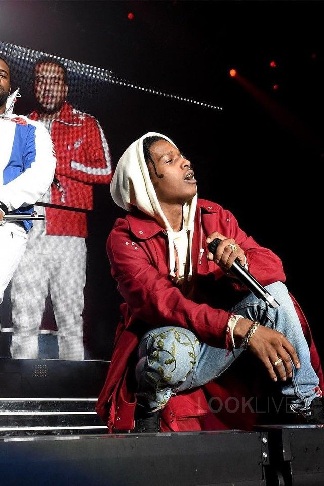 ASAP Rocky wearing  Raf Simons Eyelet Coat, Gucci Embroidered Denim Pants, Gucci Resort 17 Vintage Logo Hoodie