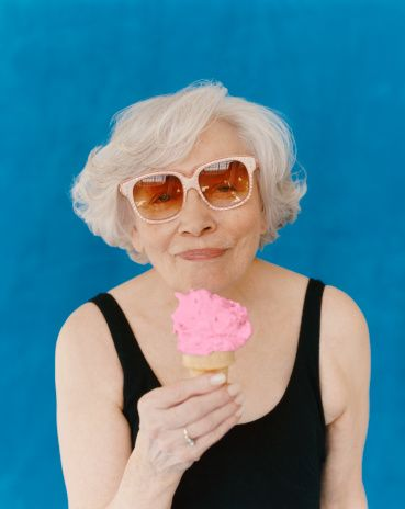 Stock Photo : Senior Woman Wearing Sunglasses and a Swimming Costume Eating an Ice Cream