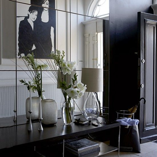 A dramatic entryway in black. I love it all! Especially the black and white portrait and mirrors!