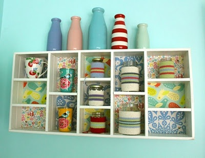 A painted and papered box filled with crocheted cups