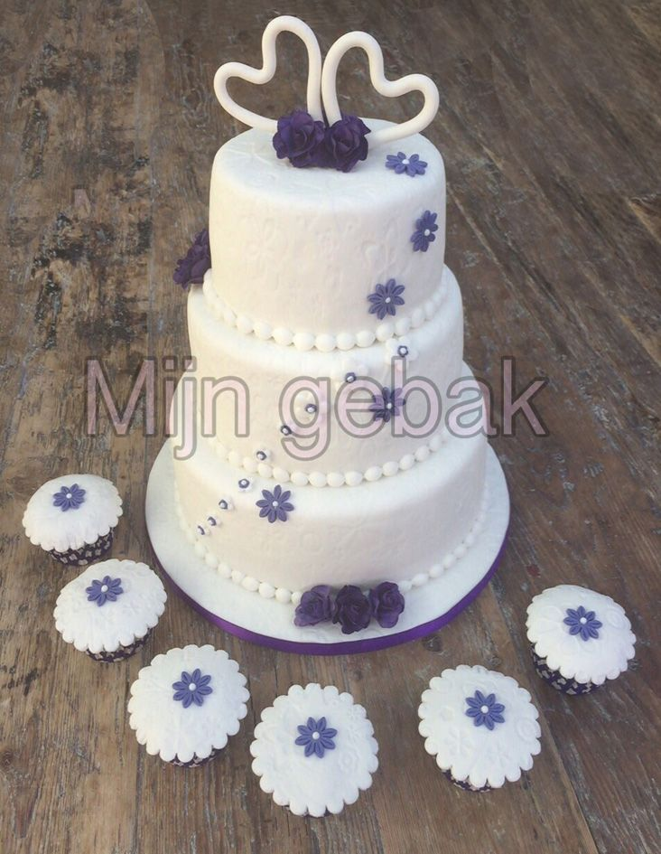 Bruidstaart met paarse afwerking en bijbehorende cupcakes