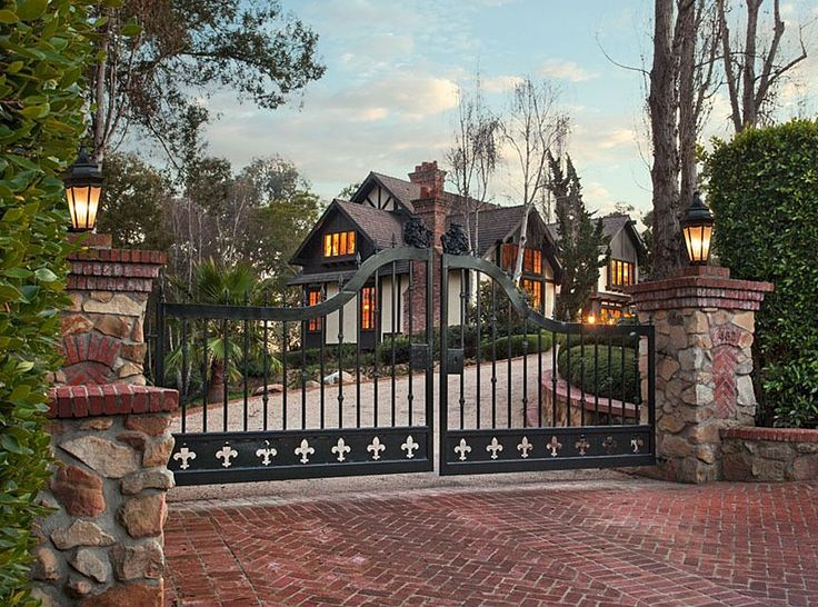 Set behind stately iron gates and tall hedging sits this English country style home within the Pepper Hill area of Montecito. #fence #brick #dreamhome