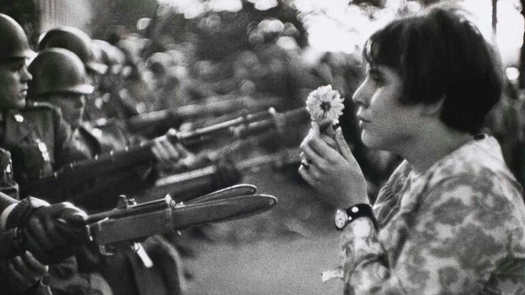 """Marc Riboud. """"Mujer con una flor"""" (1967). El famoso reportero gráfico francés logró imágenes icónicas durante sus coberturas. Lejos del dramatismo, esta fotografía ilustra un momento referencial durante las protestas en Washington por la Guerra de Vietnam. Frente al Pentágono, el 21 de octubre de 1967, el autor inmortalizó el rostro de Jane Rose Kasmir"""
