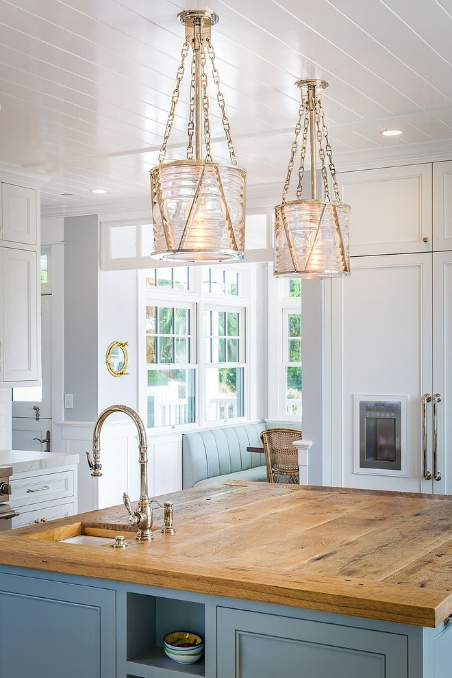 The kitchen island features custom reclaimed wood countertop. The lighting is Visual Comfort Ralph Lauren Chatham Lantern. Kitchen Faucet: Waterstone. Cabinet Hardware: similar: Appliance Pulls, Drawer Pulls & Knobs.