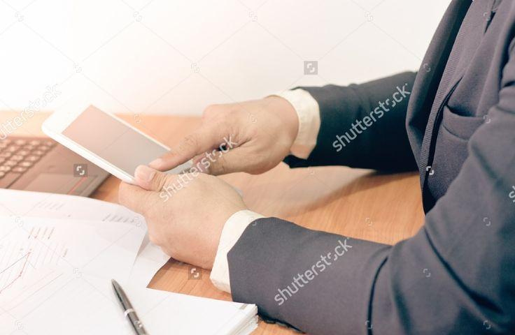 Businessman working on office desk. businessman touching a tablet screen. Blurred background, Vintage concept. #business #businessman #man #professional #office #background #notebook #tablet