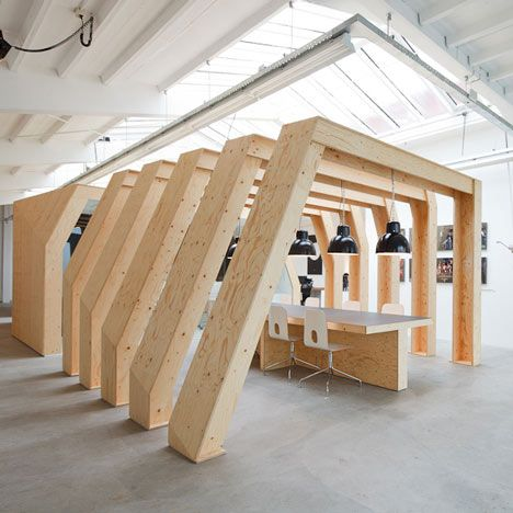 Dutch practice Origins Architects have designed this office in Amsterdam for motion graphic designers Onesize, incorporating a row of free-standing timber arches over a meeting table.