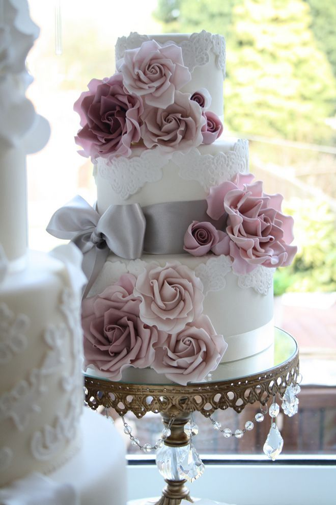 White wedding cake with lace-like pattern, silver grey satin bow, and mauve and pink fondant or sugar flowers— I need to incorporate black f...