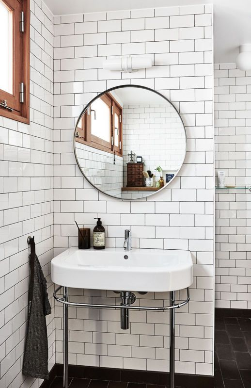 A dark grout for the white subway tiles offers a unique layer of contrast to the walls, complementing the adverse combo on the floors.