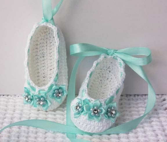 Crochet baby ballerina slippers in white with soft teal accents - Adorned with mini ribbon flowers that have pearls and rhinestone at center - Also embellished with teal satin ribbon that can be laced up baby