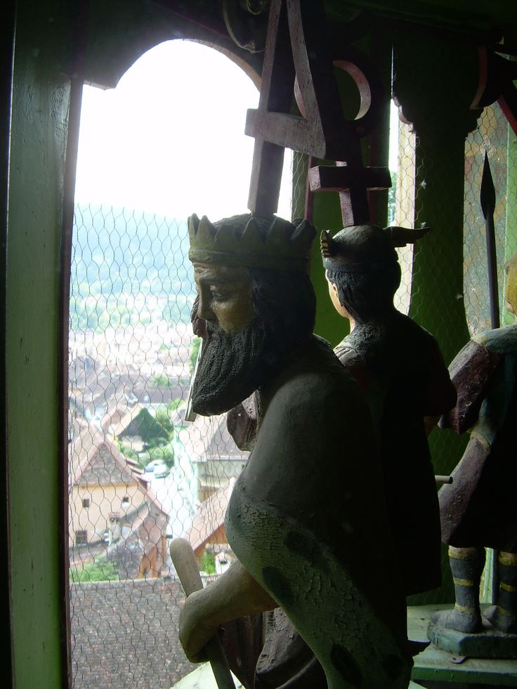Creepy medieval puppet looks out the 13th century clocktower - Sighisoara, Romania