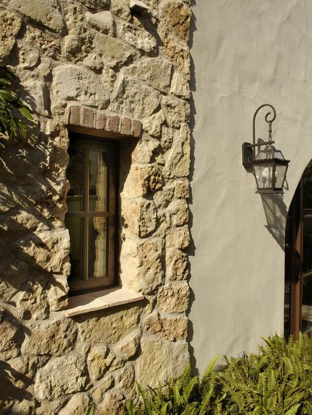 Stone Exterior Wall: Uneven stone wraps around a recessed ...