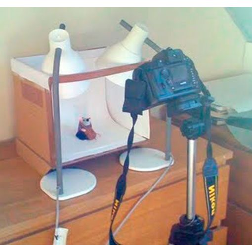 Улучшаем качество фото изделий ручной работы Если вы продаете товары через интернет, очень важно делать красивые фотографии своих изделий. Если солнце очень редко заглядывает в окна, вы можете соорудить рабочее место с искусственным освещением. Для этого нам подойдет картонная коробка. Отрезаем верх и переднюю стенку, но не до конца, а оставив в верхней части перемычку. Это делается для того, чтобы наша коробка продолжала держать свою форму. Начинаем выстилать стенки коробки листами белой…