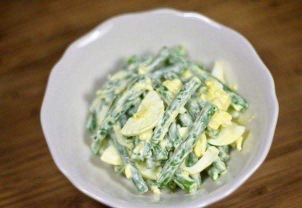 Салат из зеленой фасоли с яйцами  Ингредиенты:  - 400 г зеленой фасоли - 4 яйца - 1-2 зубчика чеснока, очищенных - 1 столовая ложка сливочного масла - майонез по вкусу  Приготовление:  1. Отварите яйца и залейте холодной водой. 2. Очистите и нарежьте зеленую фасоль. Вскипятите воду, посолите по вкусу, добавьте фасоль и отварите 3. зеленую фасоль обжарьте с маслом 4. Переложите жареную фасоль в салатник, выдавите сверху чеснок. 5. Очистите яйца и нарежьте их в салатник с фасолью.