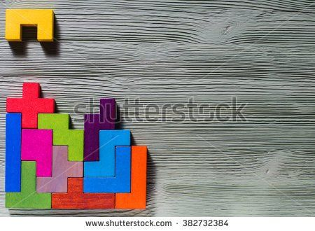 The concept of logical thinking. Geometric shapes on a wooden background.  Tetris toy wooden blocks. - stock photo