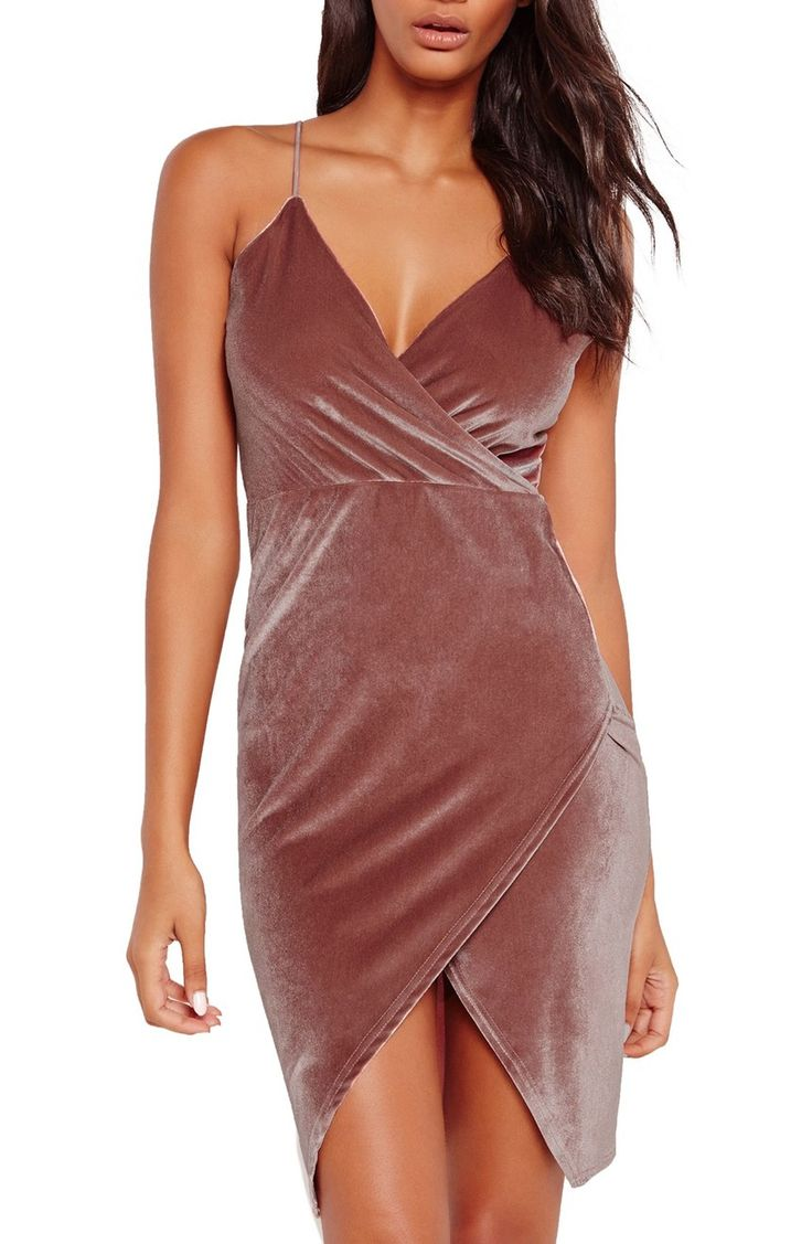 Slender spaghetti straps suspend this sophisticated wrap dress cut from impeccably soft and plush velvet. A chic asymmetrical hem finishes the party-ready piece.