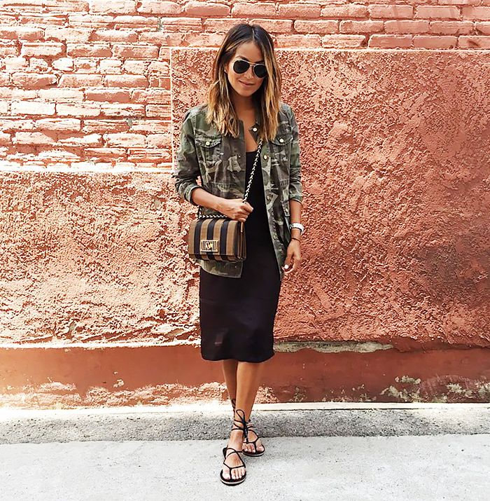 Sincerely Jules ina black dress, camo print military jacket, brown and black striped crossbody bag, black lace up sandals, and aviator sunglasses