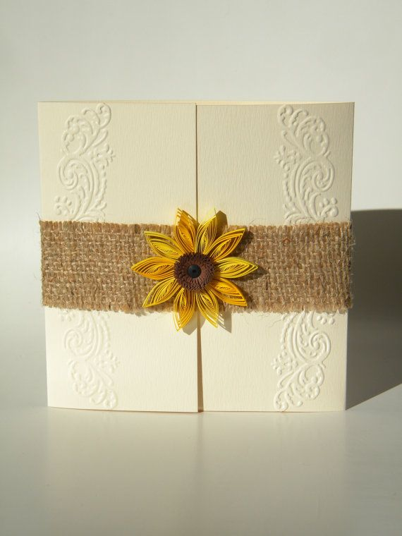A burlap ribbon and a beautiful quilled sunflower with fringed center. It would fit for a rustic sunflower wedding theme.
