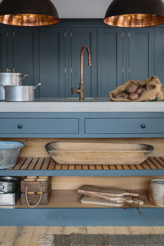 Farrow & Ball Down Pipe painted oak cabinets in an industrial shaker style showroom kitchen. The island has a polished concrete worktop and open shelving with slatted wood. The hanging industrial pendant lights from Original BTC and the bespoke copper tap adds continuity to the space. The floors are made from reclaimed scaffold planks.