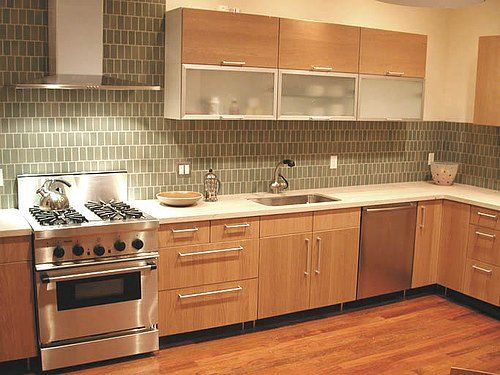 A modern style range hood and small, monotone tiles complete the contemporary look of this elegant kitchen.