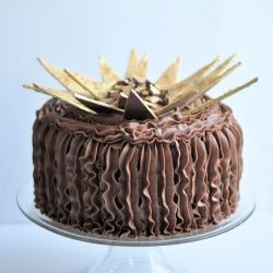 Chocolate cake, chocolate frosting topped with a golden chocolate design.